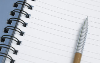 Mechanical pencil lying on the lined blank page of a ringbound notepad